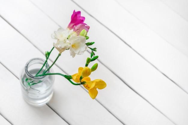 Вид сверху красивых весенних цветов на белом деревянном фоне с пространством для текста, выборочный фокус