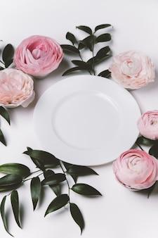 花と白いプレートと美しいテーブルセッティングの上面図