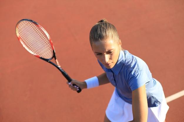 테니스 코트에서 공을 제공할 준비가 된 아름다운 테니스 선수의 최고 전망.