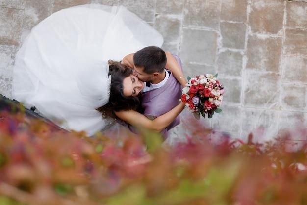야외에서 키스하는 웨딩 부케와 아름다운 웨딩 커플의 상위 뷰, 결혼 개념