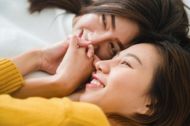 함께 누워있는 동안 포옹하고 웃는 아름다운 젊은 아시아 여성 레즈비언 행복한 커플의 상위 뷰