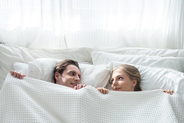 Взгляд сверху красивых молодых кавказских пар пряча под одеялом и смотря один другого с улыбкой и потехой пока лежащ в кровати в утре вверх по дому.