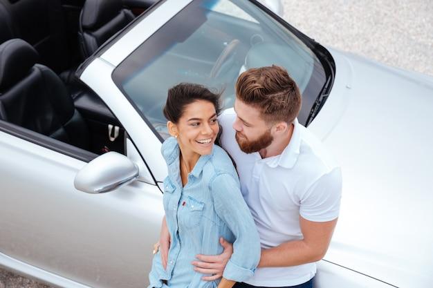 Вид сверху красивой молодой пары, обнимающейся, стоя возле автомобиля на берегу моря