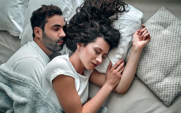 自宅のベッドで一緒に寝ている間抱き締める美しい若いカップルの上面図