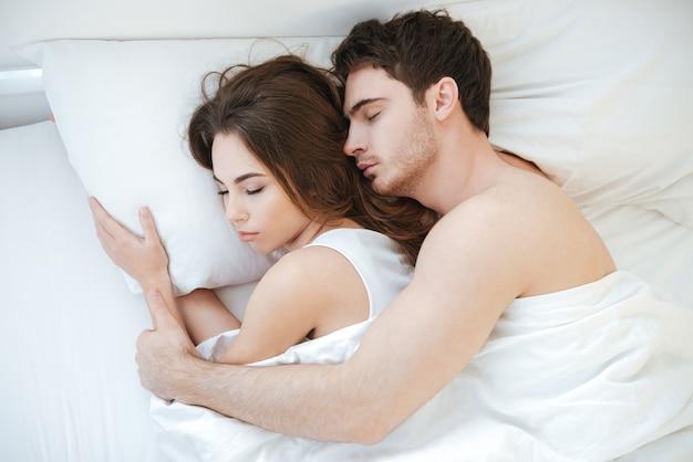 Вид сверху красивой молодой пары, вместе спящей в постели