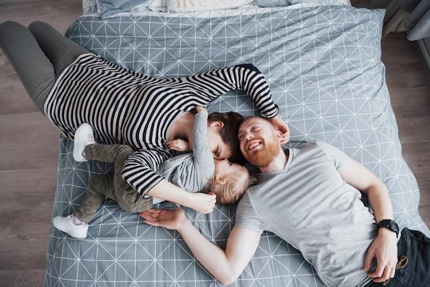 美しい若い母親、父親と娘のカメラ目線とベッドに頭の上に横たわっている間笑顔の平面図