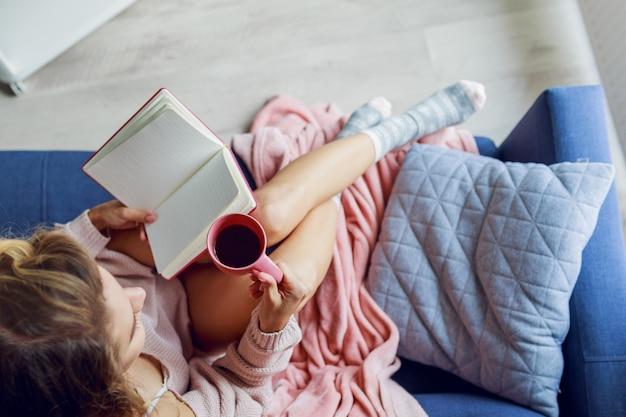 自宅のソファでリラックスしながら一杯のお茶を保持している美しい若い女性の平面図です。暖かい居心地の良い朝の時間。