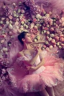 花に囲まれたピンクのバレエチュチュの美しい若い女性の上面図