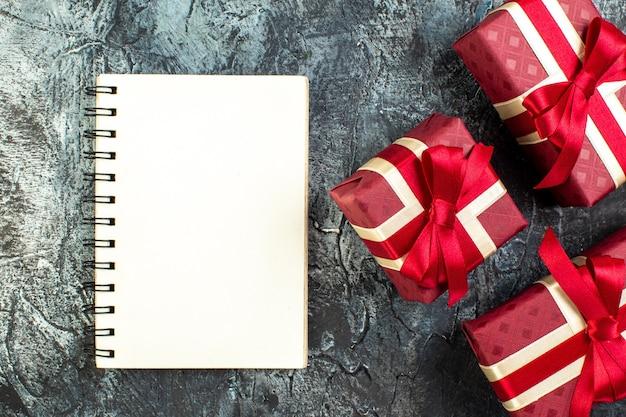 어둠 속에서 아름답게 포장된 선물 상자와 나선형 노트북의 상위 뷰