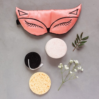 Вид сверху на косметические средства, такие как маска для сна и чистящие губки на сером