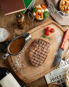 Вид сверху стейк из говядины с соусом и вареными овощами