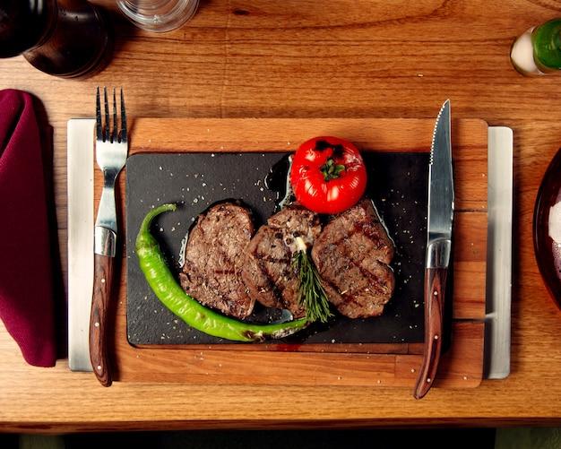 Вид сверху на стейки из говядины с помидорами на гриле и перцем