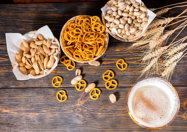 暗い木製の机の上にピスタチオ、小さなプレッツェル、ピーナッツが入ったプレートの近くに大きな泡の頭があるビアグラスの上面図。食品および飲料の概念