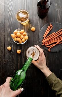 瓶からガラスの黒い木製の背景に注ぐビールのトップ ビュー