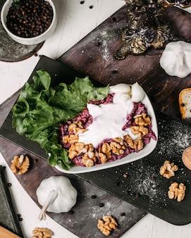 木の板にクルミとサワークリームとビートのサラダのトップビュー
