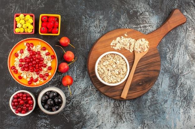 Вид сверху ягод, конфет, красной смородины, черного винограда, граната, овсянки на доске