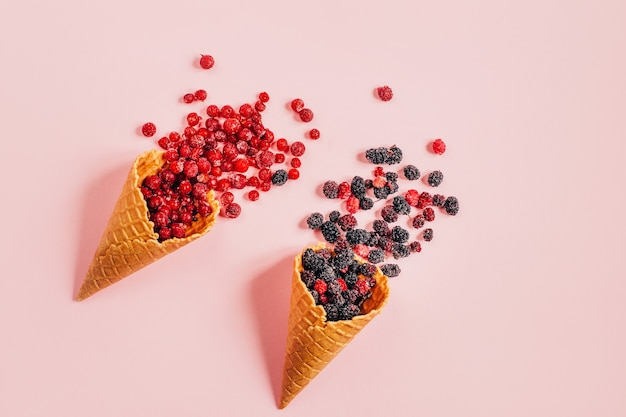 Вид сверху ягод вишни смородины шелковицы в вафельных стаканчиках на розовой поверхности
