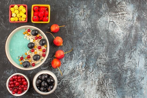 어두운 테이블에 열매 다채로운 열매 오트밀 체리의 상위 뷰