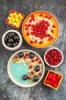 Вид сверху ягод овсянки граната желтые конфеты черный виноград вишня красная смородина