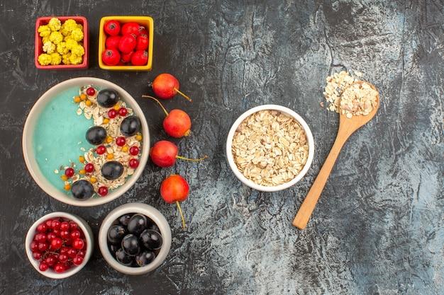 Вид сверху ягод красной смородины черный виноград красочные ягоды миска овсянки деревянной ложкой