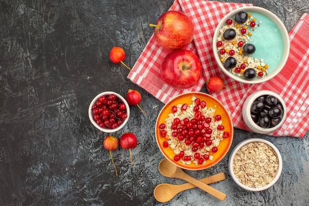 Вид сверху ягод, ложек, красной смородины, вишни, винограда, яблок, граната, овсянки в миске