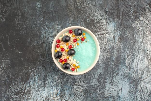 Вид сверху ягод аппетитной красной смородины и винограда в синей миске