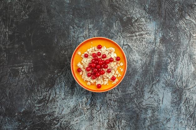 Вид сверху ягод аппетитной красной смородины на оранжевой тарелке на сером столе