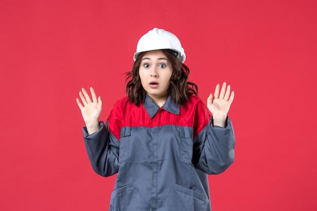 고립 된 빨간색 배경에 하드 모자와 제복을 입은 어리둥절한 여성 건축업자의 상위 뷰