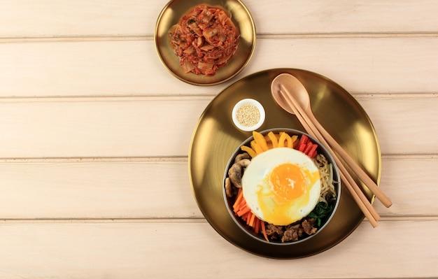 Вид сверху на пибимпап, классическую корейскую еду. рис покрыт приправленными овощами, мясом и жареным яйцом. в завершение этого пикантного азиатского блюда можно добавить острый соус чили.