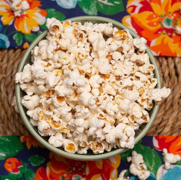 Вид сверху на большую миску, полную попкорна, над цветочной тканью на соломенном столе