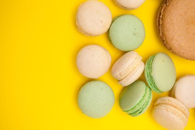 Вид сверху большого карамельного аромата миндального печенья рядом с маленькими миндальным печеньем на желтом фоне. ассорти из десертов