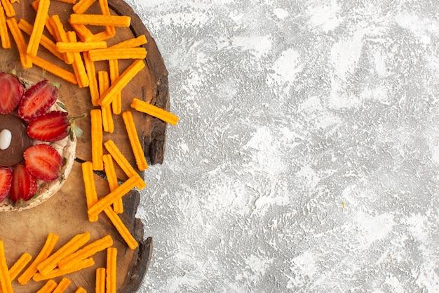 木製の机と光の表面のケーキ甘いデザートフルーツシュガーベークにオレンジラスクとイチゴのビスケットのトップビュー