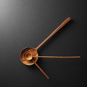 검정색 배경에 나무 숟가락이 있는 검정색 알람 시계의 상위 뷰 - 개념 및 아이디어