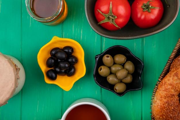 緑の木製の背景の上のバケツにパンとガラスの瓶に蜂蜜とボウルに黒と緑のオリーブの上面図