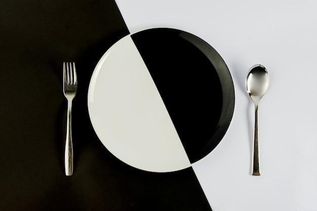 Вид сверху черно-белой тарелки с серебряной ложкой и вилкой на черно-белом столе