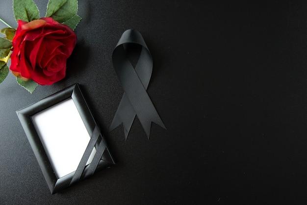 暗い壁に赤い花が付いている黒い弓の上から見る
