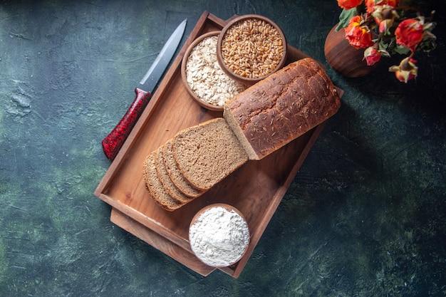 파란색 배경에 갈색 나무 쟁반에 검은 빵 조각 밀가루 메밀 오트밀의 상위 뷰