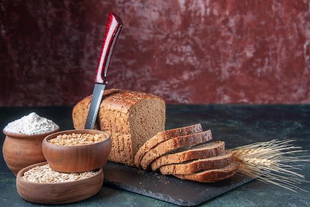 혼합 색상 고민 배경에 어두운 색상 보드에 검은 빵 조각 밀가루 오트밀 메밀의 상위 뷰