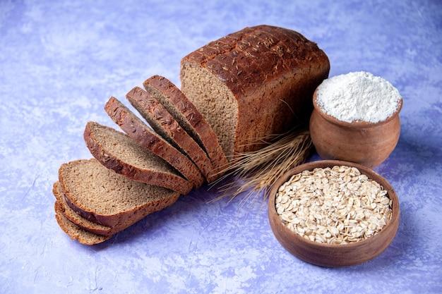 空きスペースのある水色のパターンの背景に黒いパンのスライス小麦粉オートミールの上面図