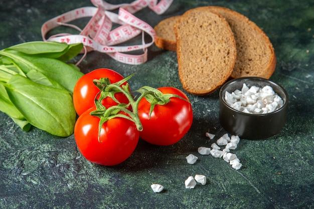 黒いパンの上面図は、暗い表面に茎とメートルの緑の束の塩で新鮮なトマトをスライスします