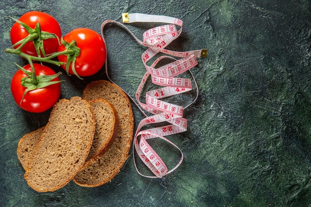 Вид сверху на ломтики черного хлеба из свежих помидоров со стеблем и метрами с правой стороны на фоне темных цветов