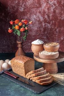 혼합 색상 고민 배경에 나무 보드 계란에 어두운 색상 트레이 밀가루 오트밀 메밀에 검은 빵 조각 칼의 상위 뷰