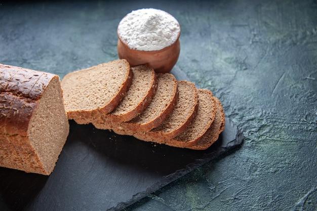 暗い色の背景に黒いトレイと茶色のボウルに小麦粉の黒いパンのスライスの上面図