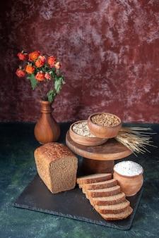黒のトレイに黒パンのスライスと栗色の背景に茶色のボウルに小麦粉の上面図