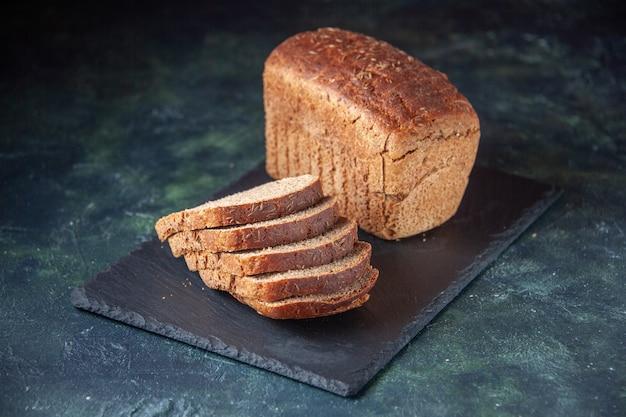 青い色の苦しめられた背景の上の黒い木製トレイの黒いパンのスライスの上面図