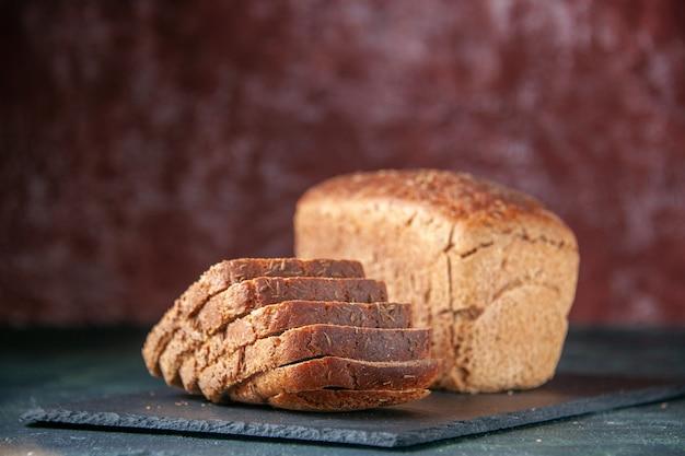 混合色の苦しめられた背景の上の黒い木製トレイの黒いパンのスライスの上面図