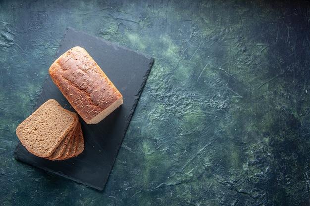 青い色の苦しめられた背景の右側にある黒い木製トレイの黒いパンのスライスの上面図
