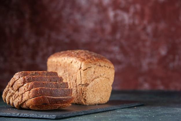 混合色の苦しめられた背景の右側にある黒い木製トレイの黒いパンのスライスの上面図