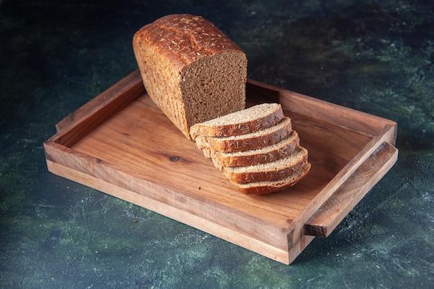 青い色の苦しめられた背景の上の茶色の木製トレイに黒いパンのスライスの上面図