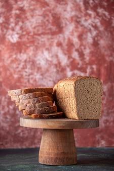 混合色の苦しめられた背景の茶色の木製トレイに黒いパンのスライスの上面図